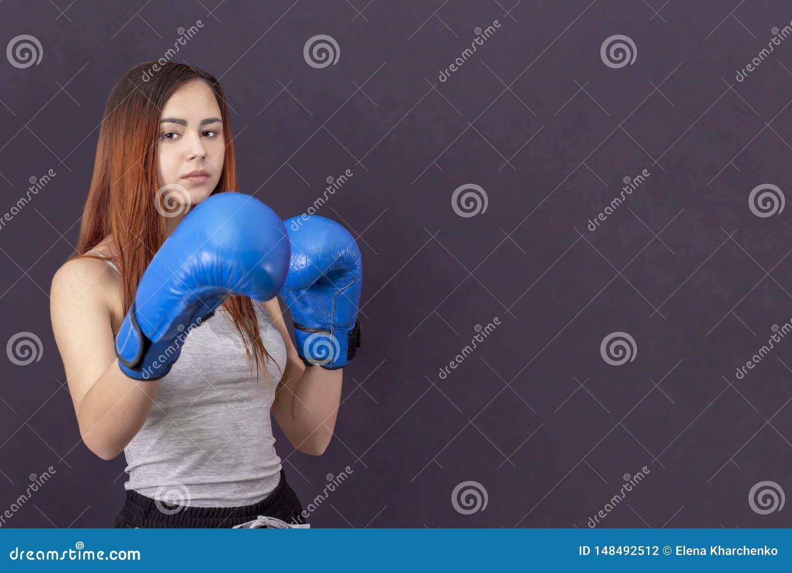 蓝色拳击手套的拳击手女孩在机架的一件灰色T恤杉