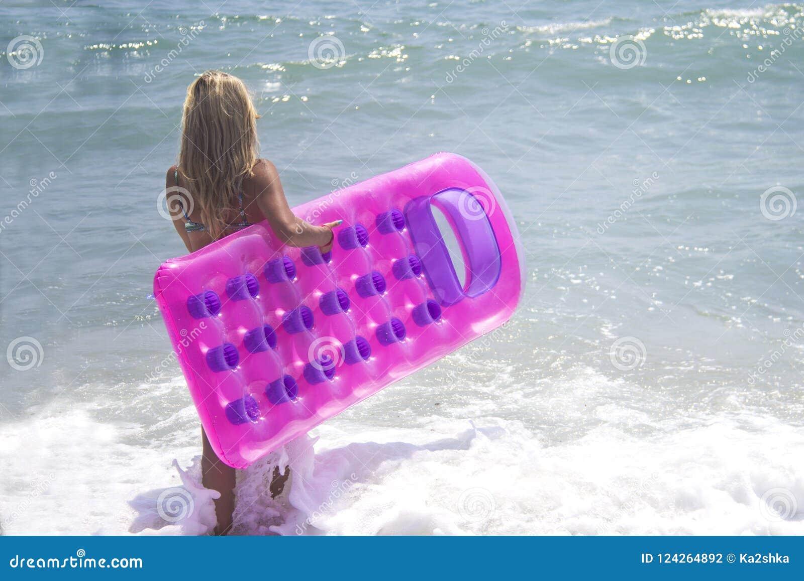 蓝色比基尼泳装的赤足女孩在海 减肥游泳衣的高女孩走在有桃红色可膨胀的水池木筏的海的