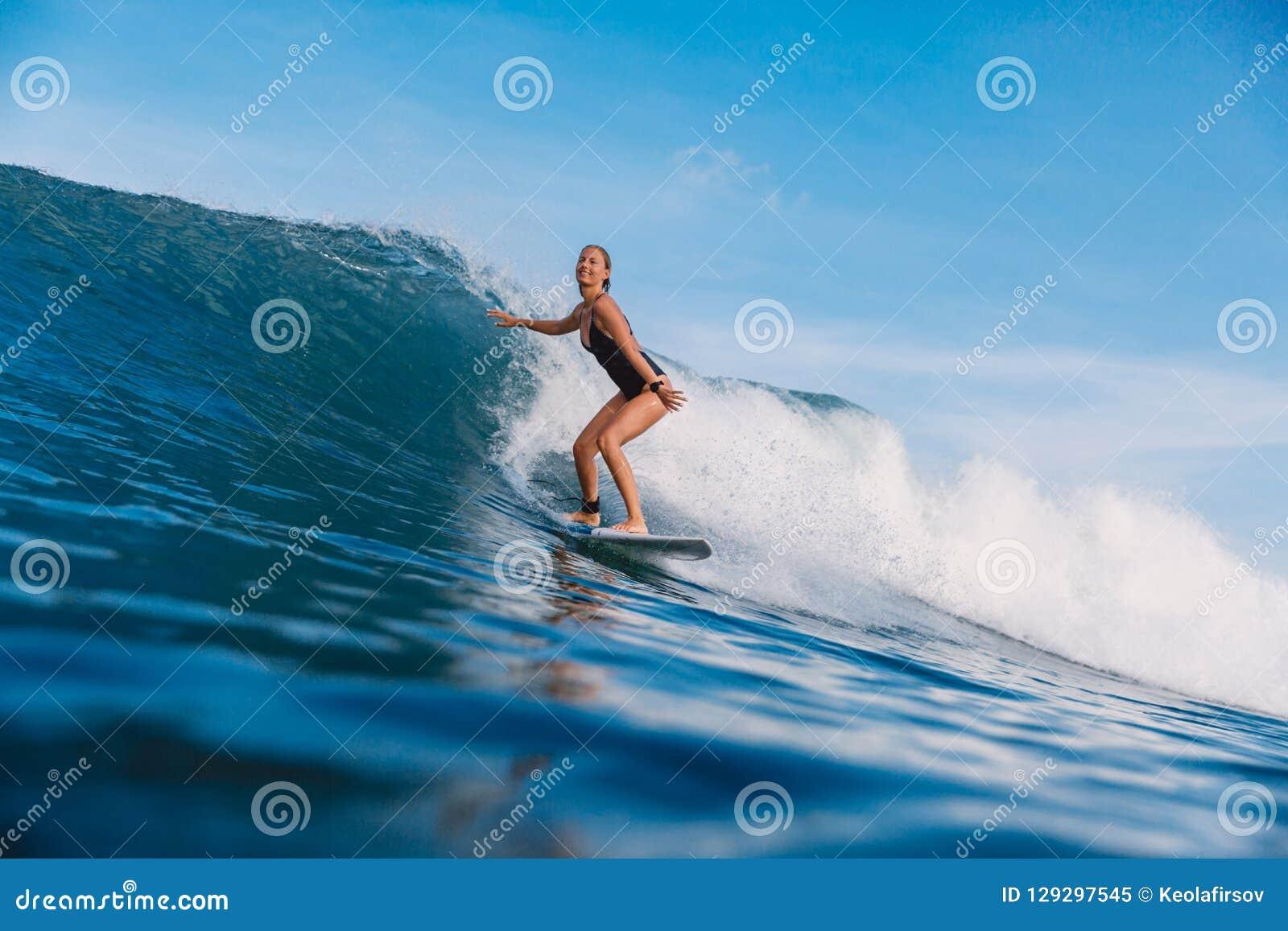 蓝色波浪的冲浪者女孩 在冲浪期间的妇女