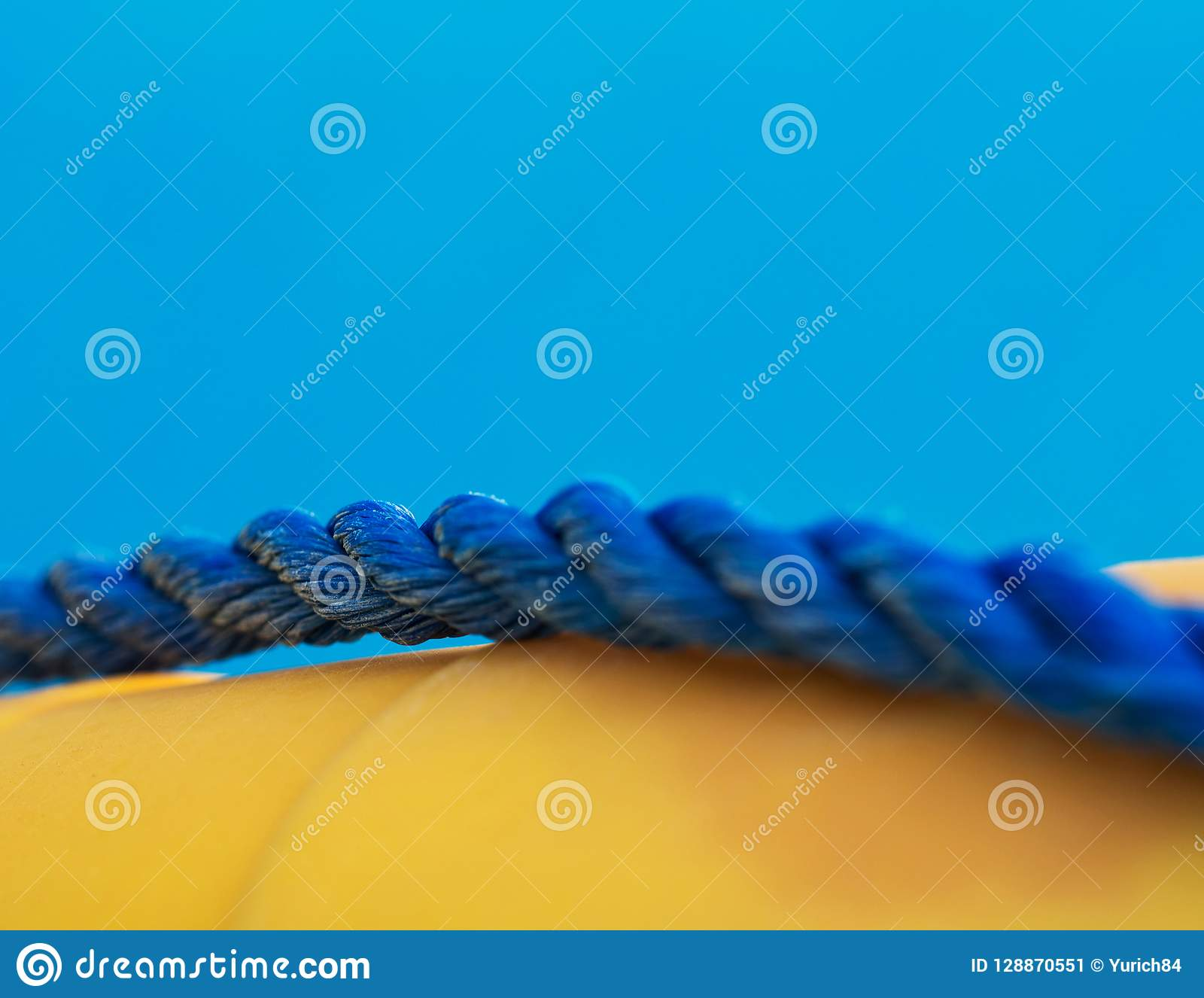 蓝色海洋扭转的绳索特写镜头在领域黄色lifebuoy,浅dept的