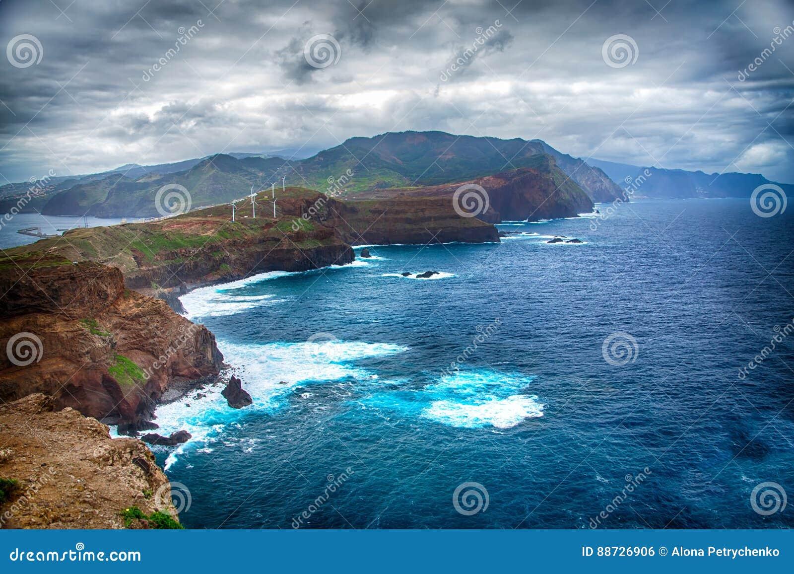 蓝色海洋、山、岩石、风车和多云天空