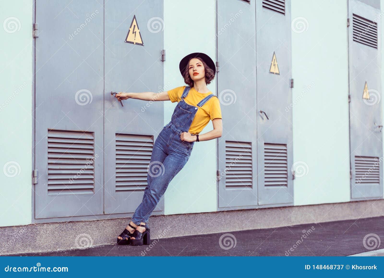 蓝色牛仔布总体和黄色T恤杉的年轻女人有黑帽会议肉欲查寻的,当摆在工厂厂房附近时