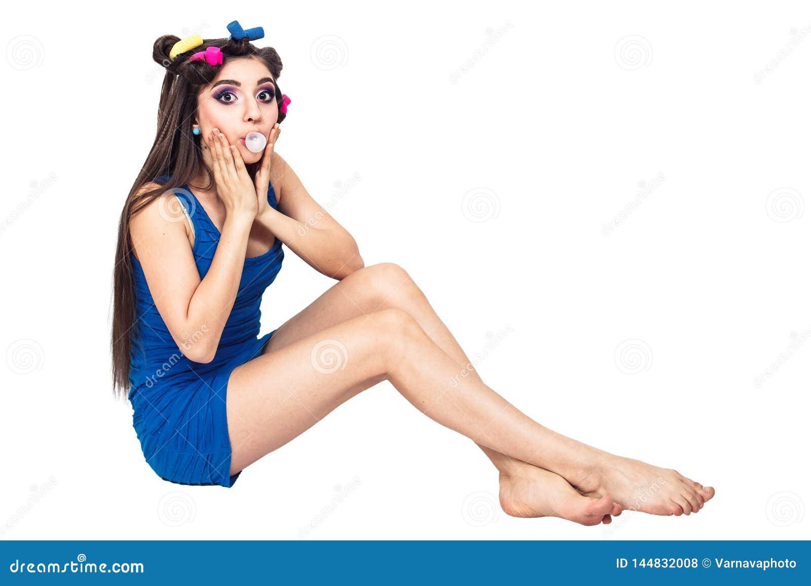 蓝色礼服的美丽的少女有卷发的人的坐地板并且嚼反刍食物