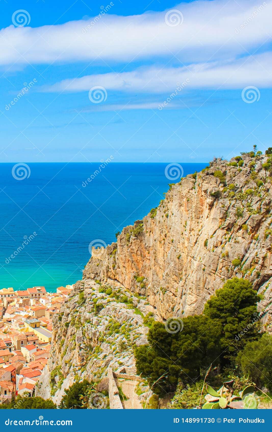 蓝色第勒尼安海令人惊讶的看法从上面采取与岩石和海滨城市切法卢用意大利语西西里岛 夺取在垂直