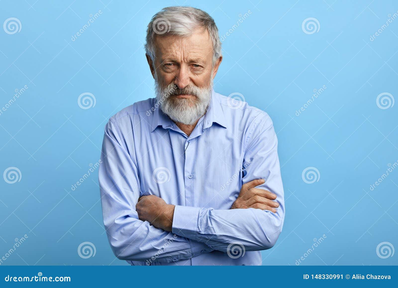 蓝色衬衣的英俊的老人有怀疑表示的
