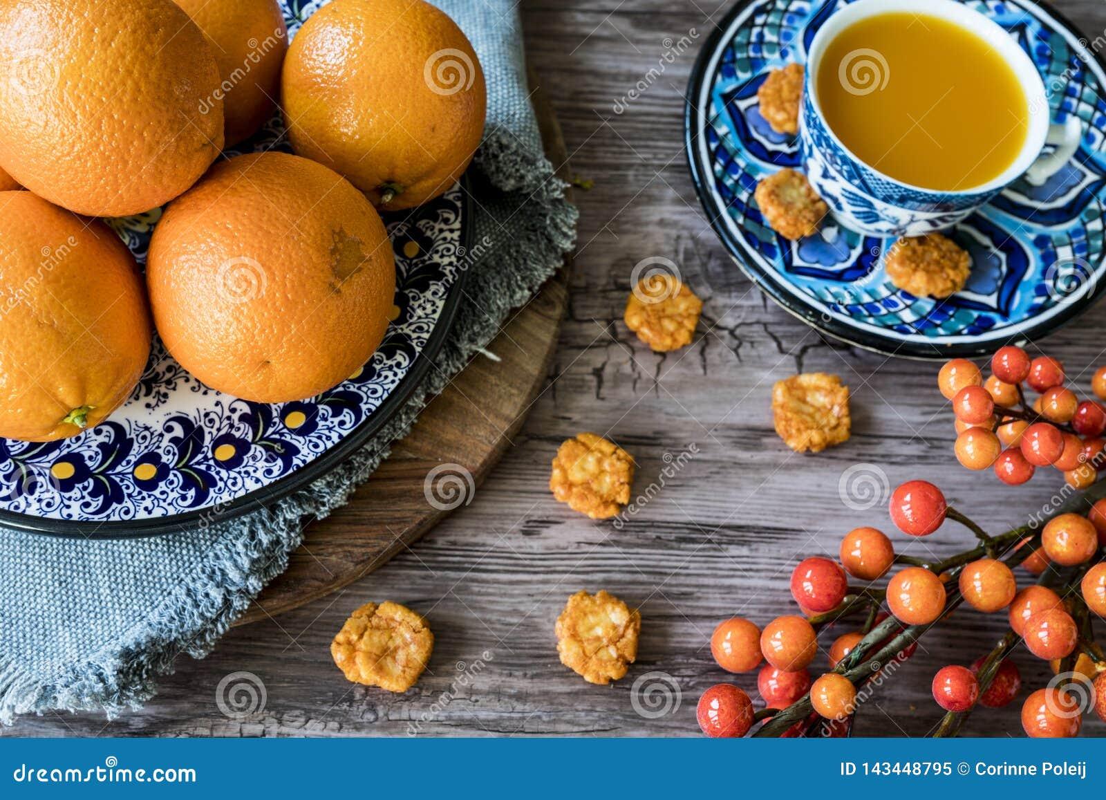 蓝色西班牙手工制造板材用桔子,莓果,在杯子的汁液在木桌上