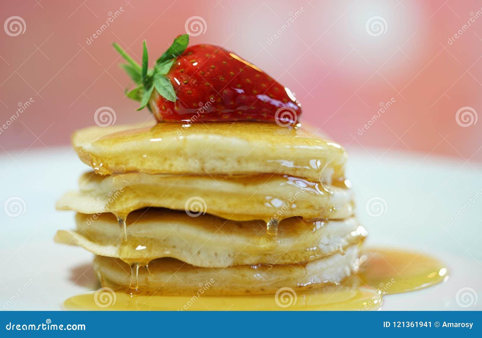薄煎饼用草莓在上面和下毛毛雨用糖浆,宏观特写镜头