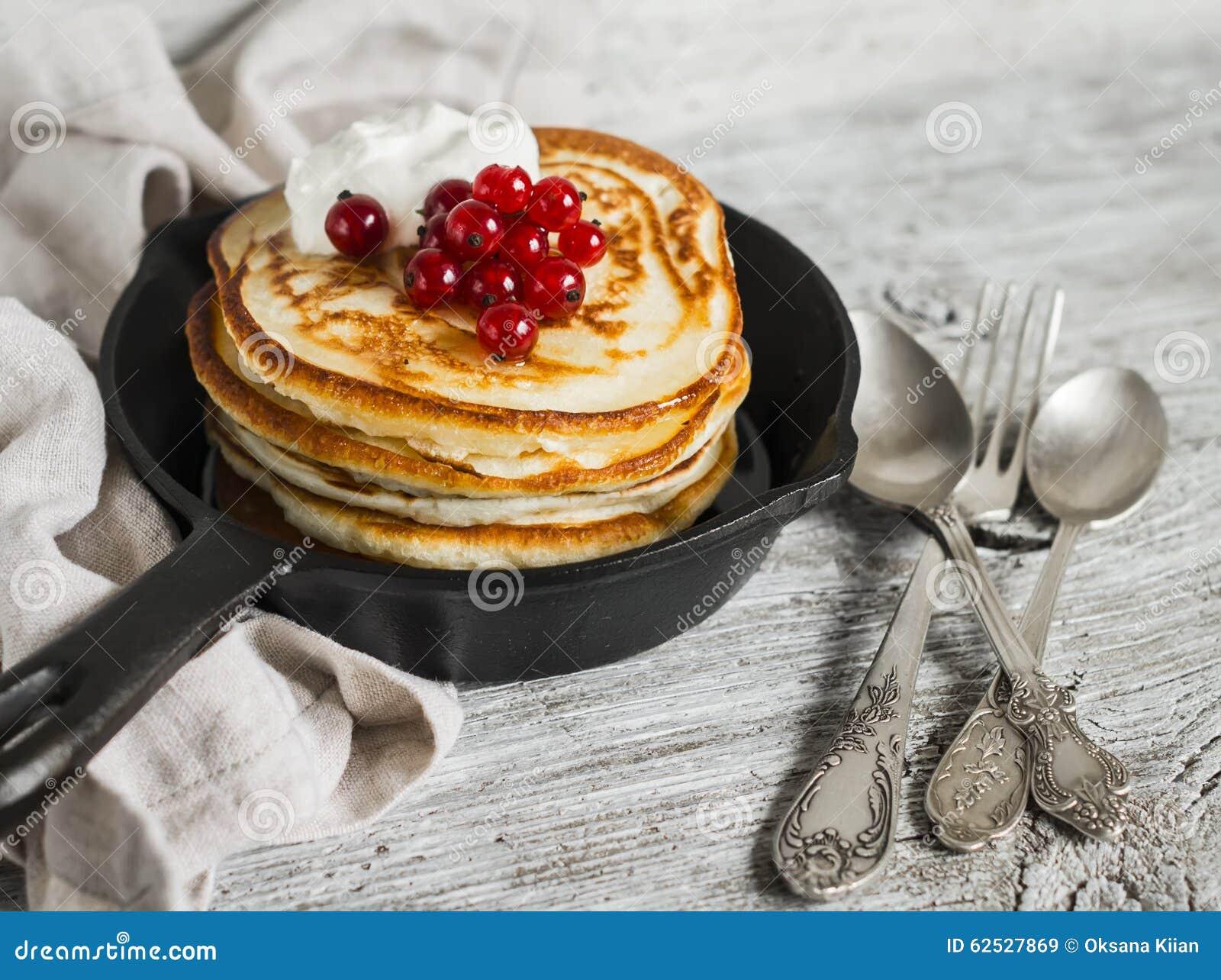 薄煎饼用蜂蜜、酸性稀奶油和红浆果在葡萄酒scourage