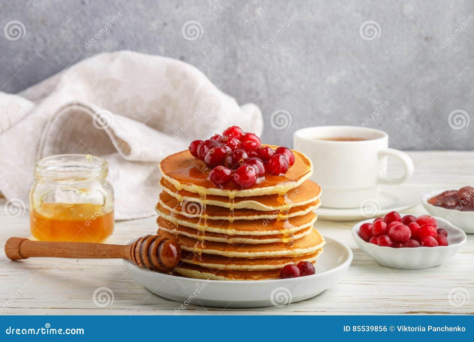 薄煎饼用蜂蜜和新鲜的莓果 蔓越桔,越橘