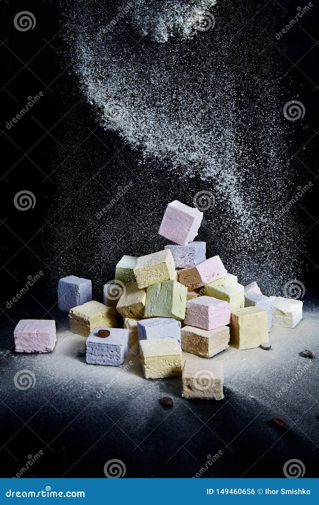 蛋白软糖洒与在黑背景的糖粉 火的自然蛋白软糖 飞行的食物 特写镜头
