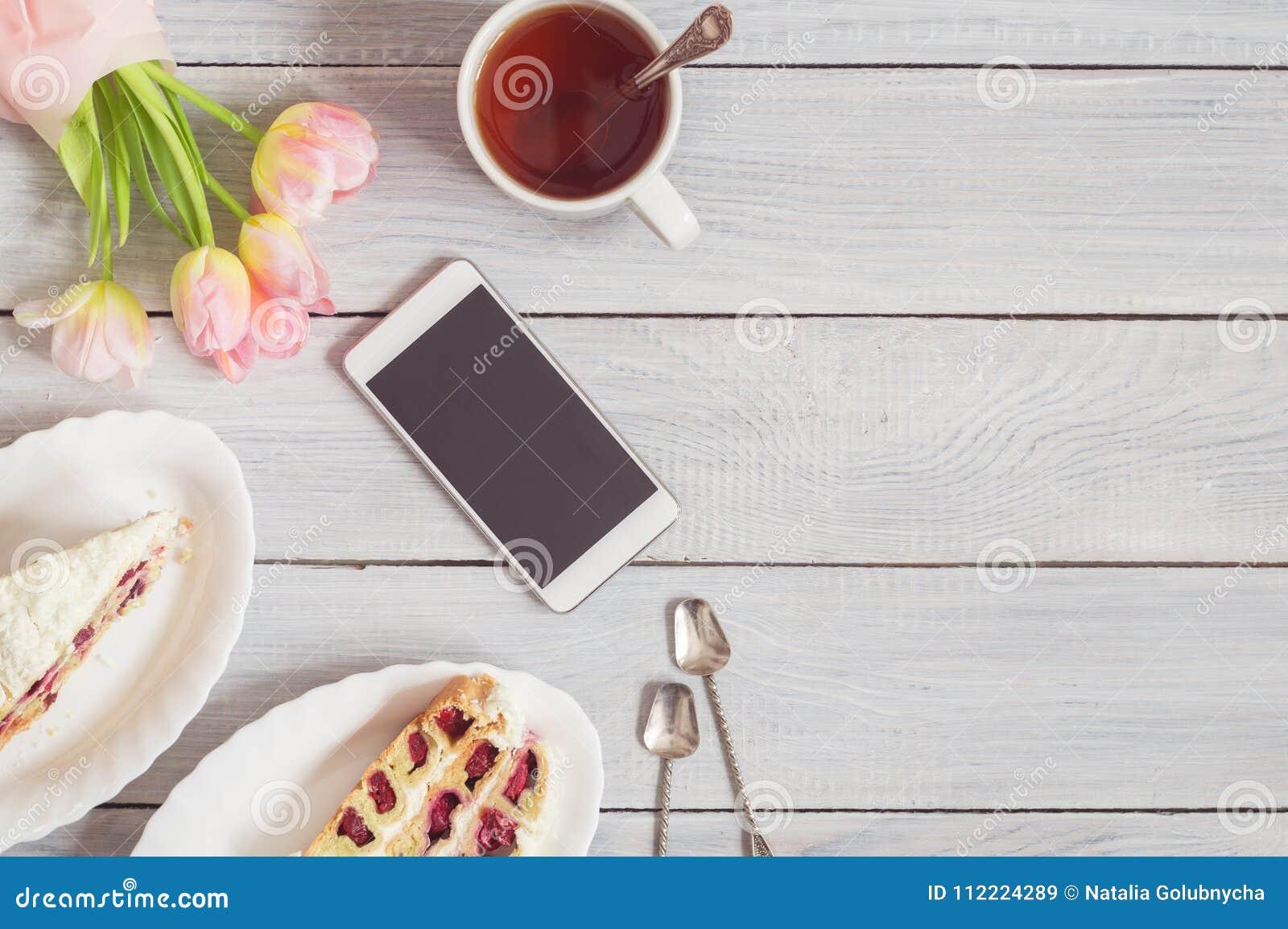 蛋糕、电话、茶和在白色木桌上的桃红色郁金香