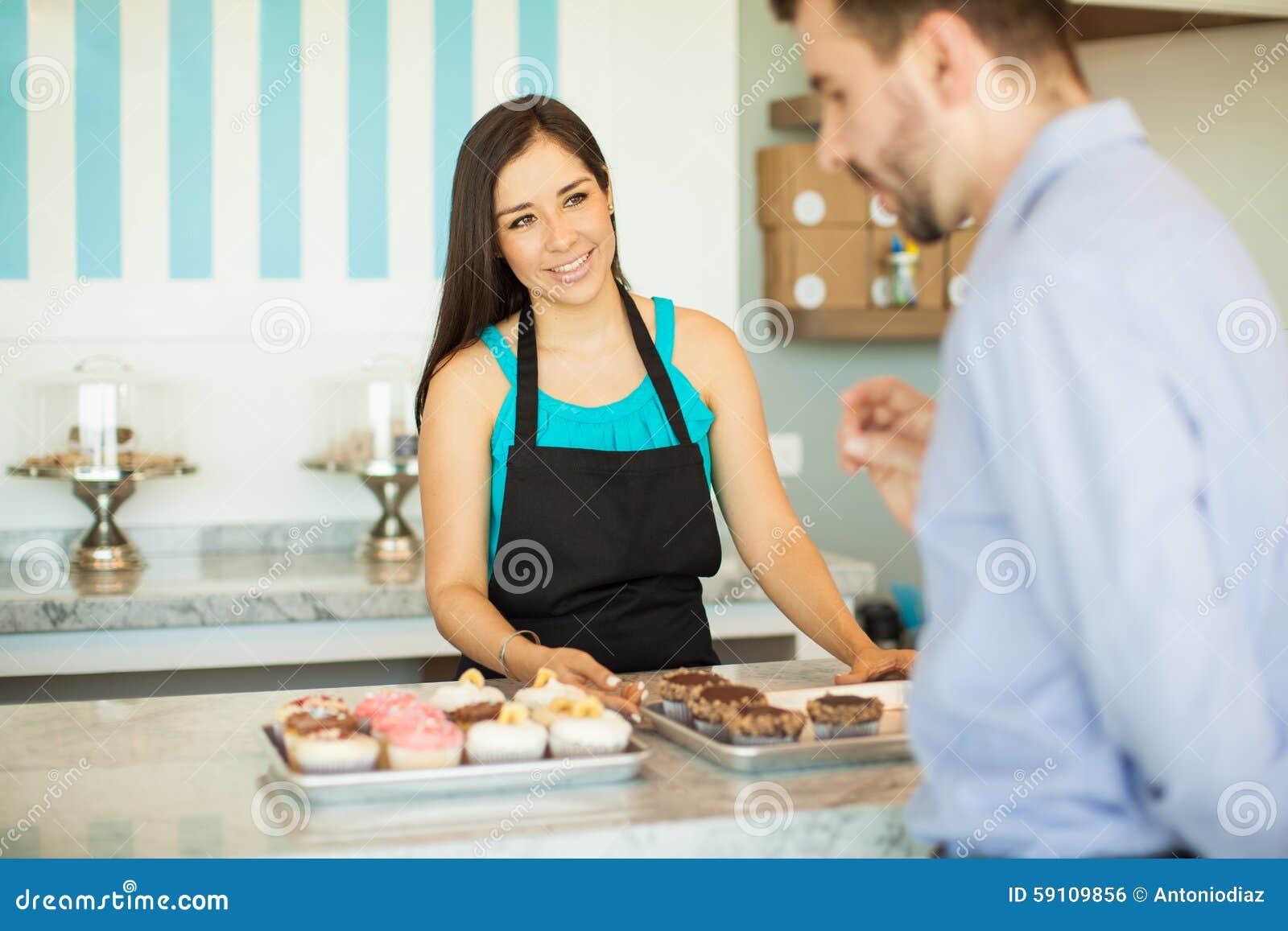 蛋糕显示杯形蛋糕的商店雇员