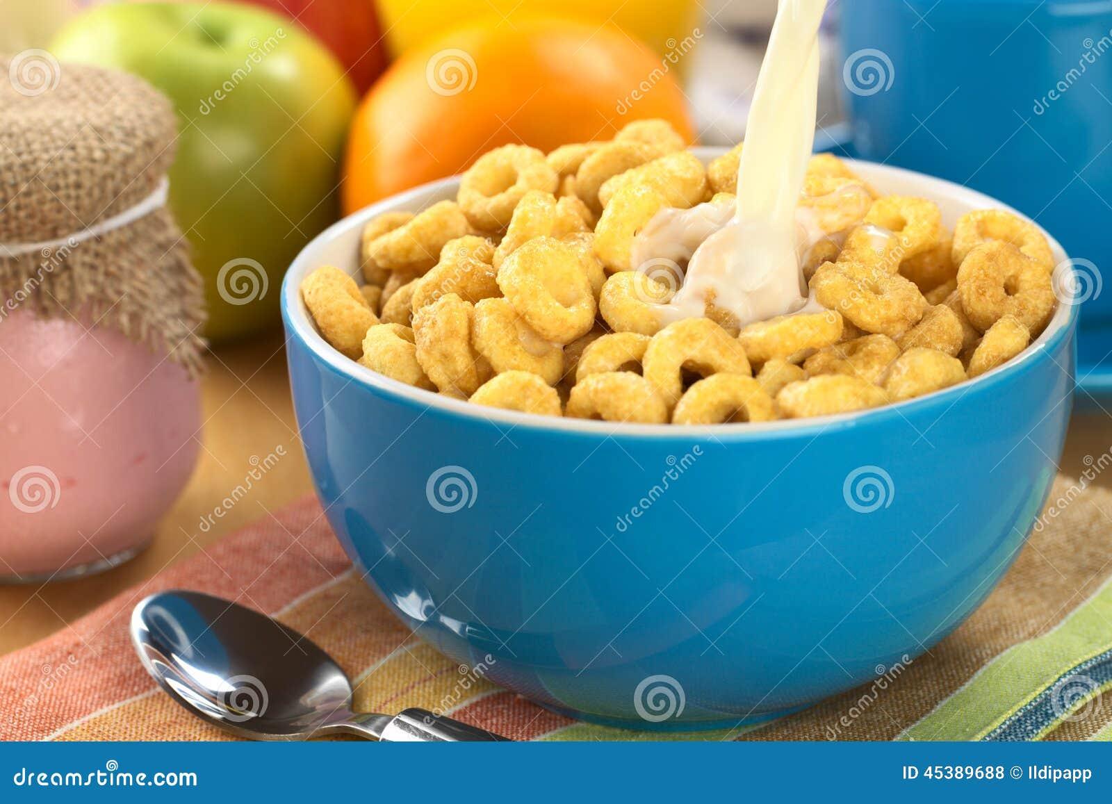 在碗的倾吐的牛奶蜂蜜充分调味了谷物圈(选择聚焦,集中于牛奶小河).图片