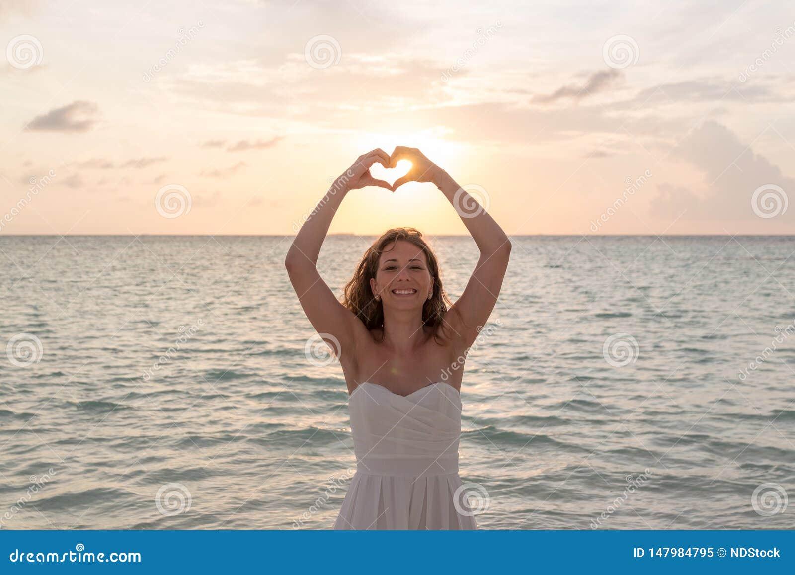蜜月框架的妇女递入心形,手指心脏框架 看和微笑对在日落期间的照相机