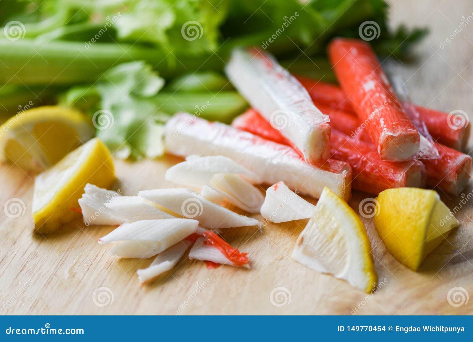 螃蟹棍子用柠檬和新鲜的芹菜菜在木板材