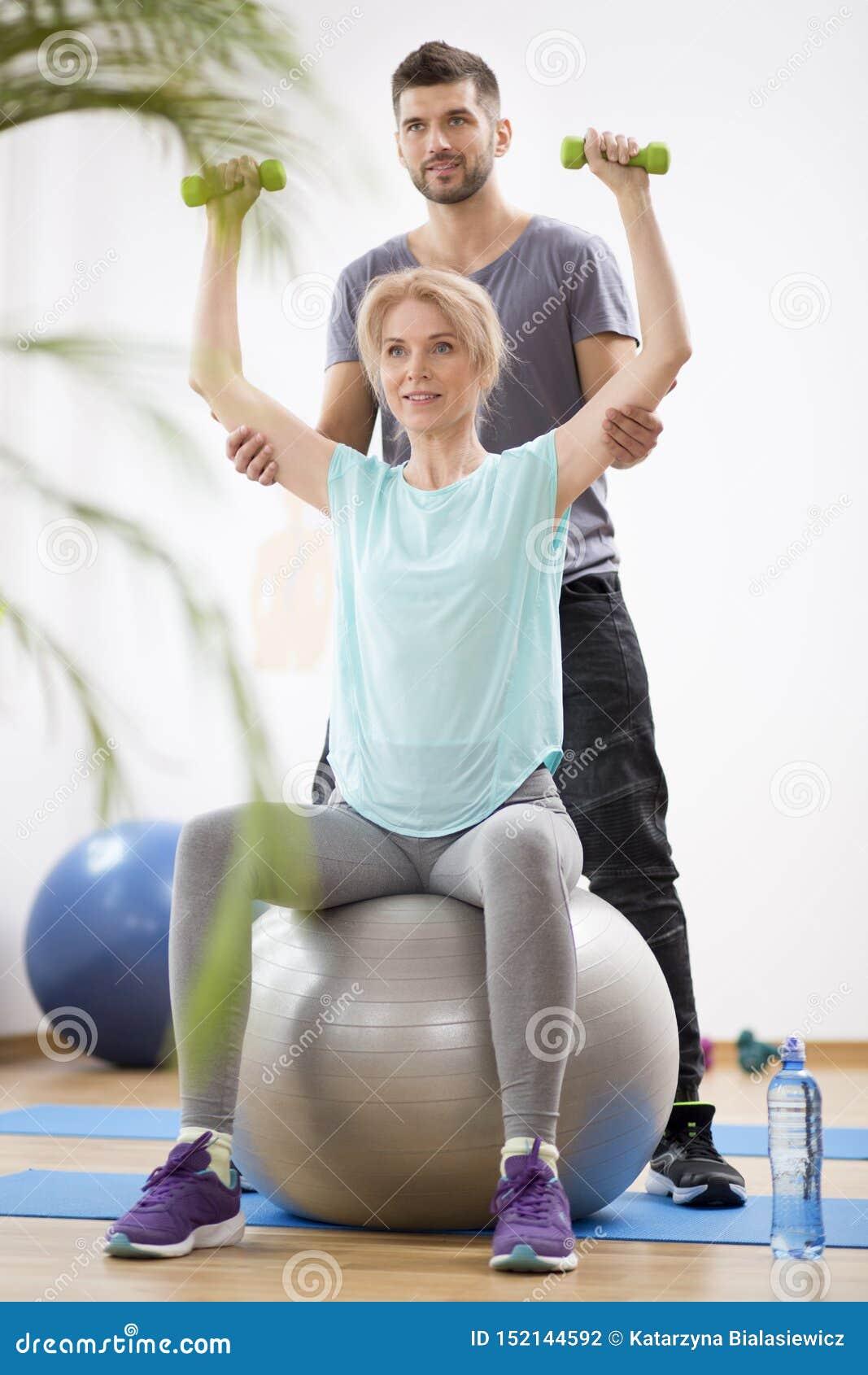 行使在体操球的中年白肤金发的妇女在与生理治疗师的会议期间