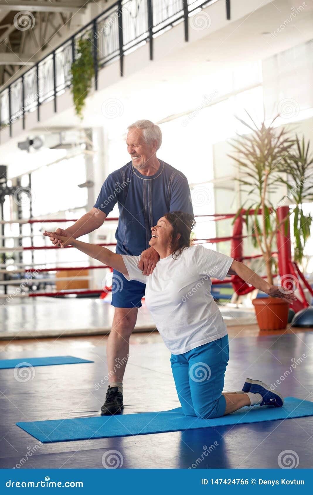 行使在健身房的活跃愉快的年长夫妇