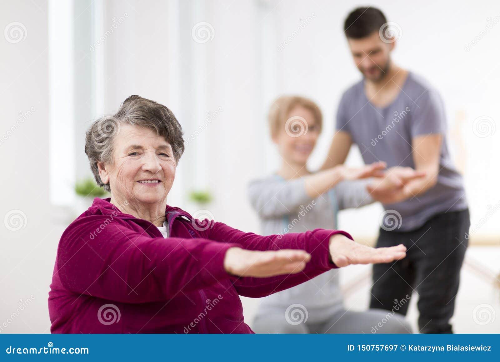 行使在小组物理疗法期间的资深夫人在康复中心