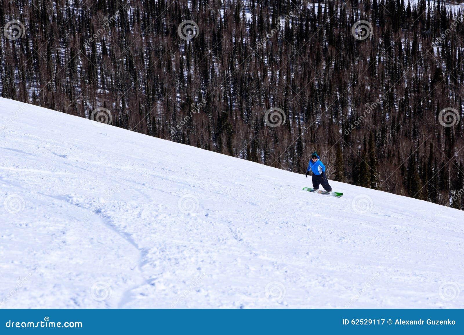 行动的女孩挡雪板在山的雪板