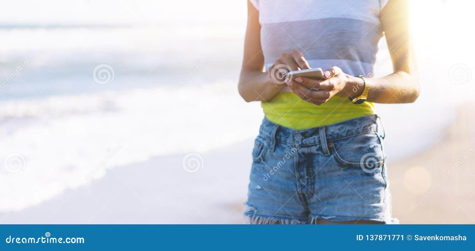 行家在智能手机小配件的女孩照片在沙子海岸线,假装黑屏 旅客举行和使用在女性手上