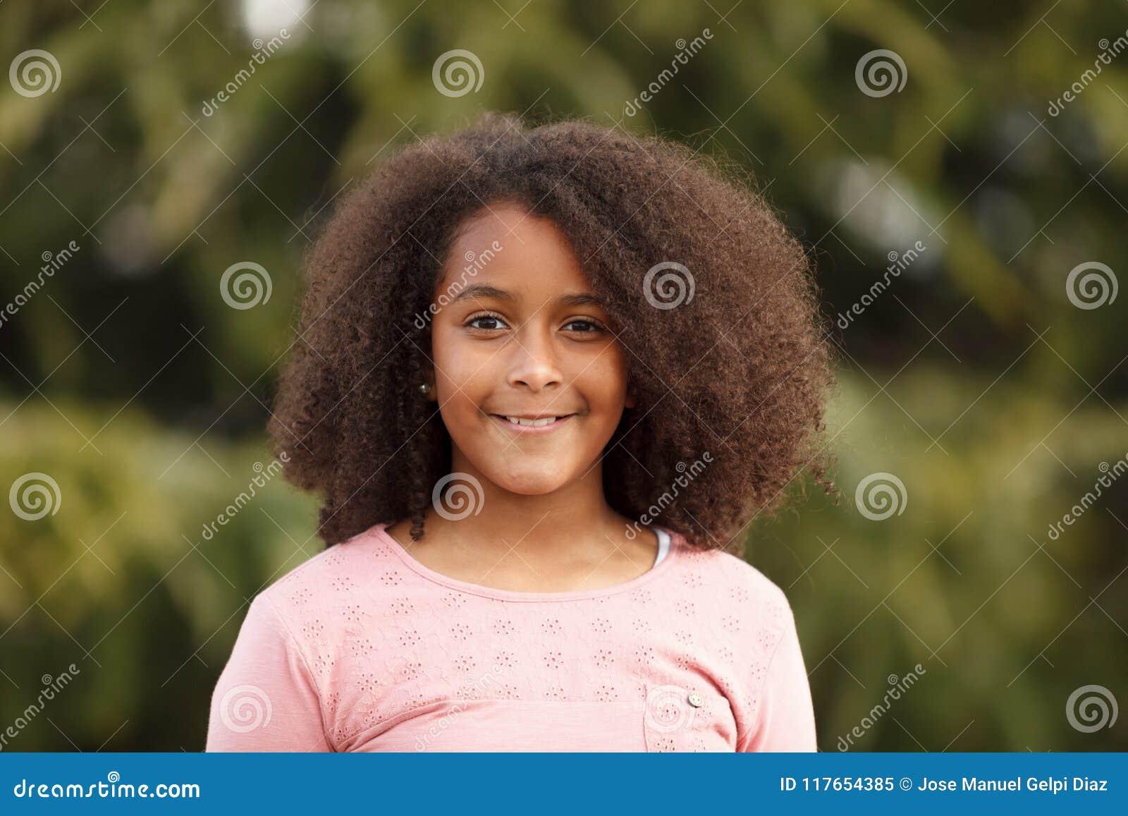 街道的逗人喜爱的非裔美国人的女孩有非洲的头发的. 愉快, 童年.
