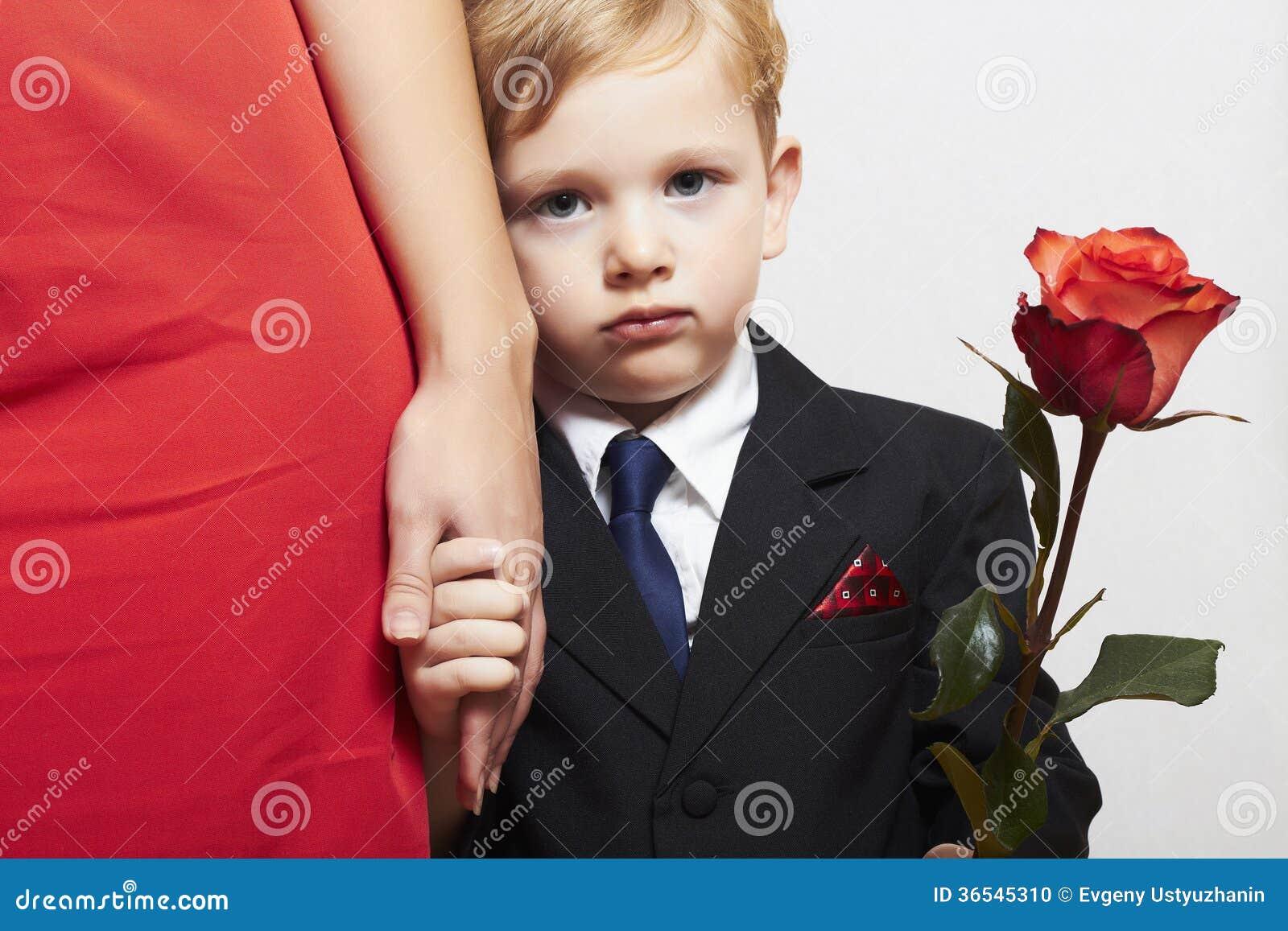 衣服的孩子与母亲。花。红色礼服。家庭。时兴的小男孩。红色玫瑰。采取手