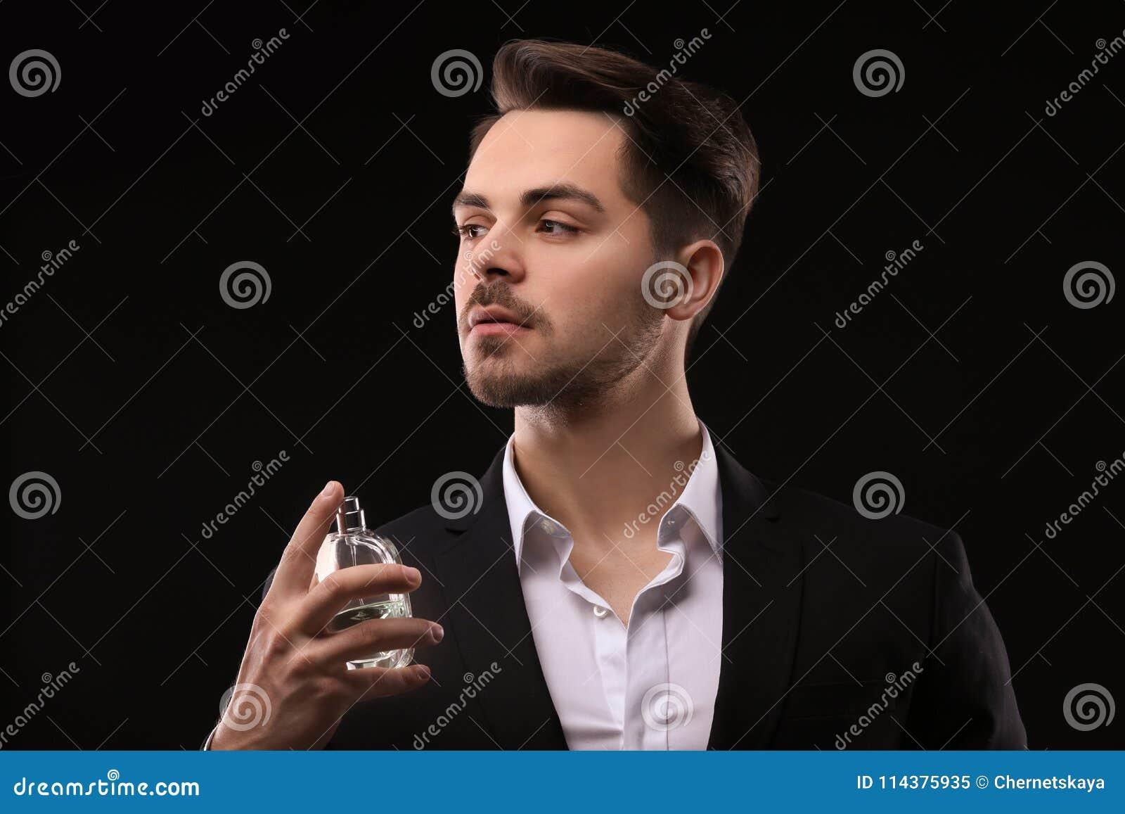 衣服的英俊的人使用香水