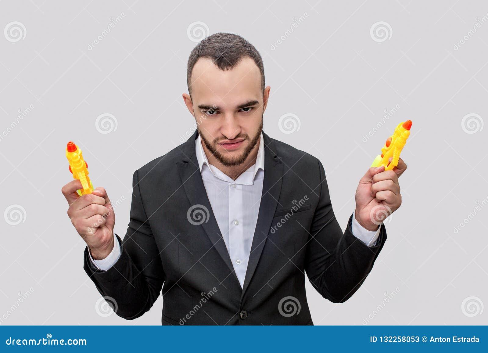 衣服立场和神色的嬉戏的年轻人在照相机 他摆在 人拿着两个黄色水枪 他恼怒 查出