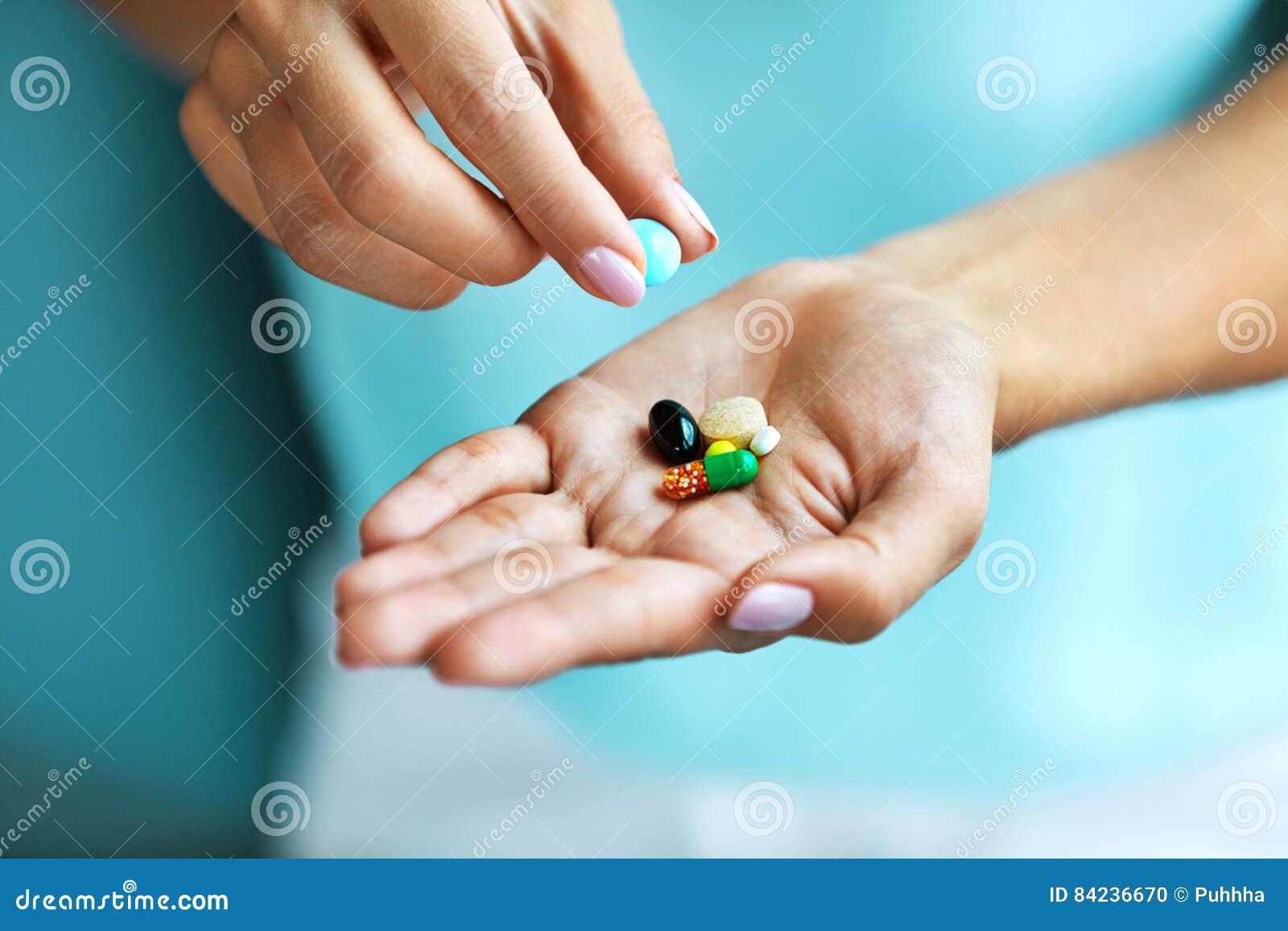 补充维生素 拿着五颜六色的药片的女性手