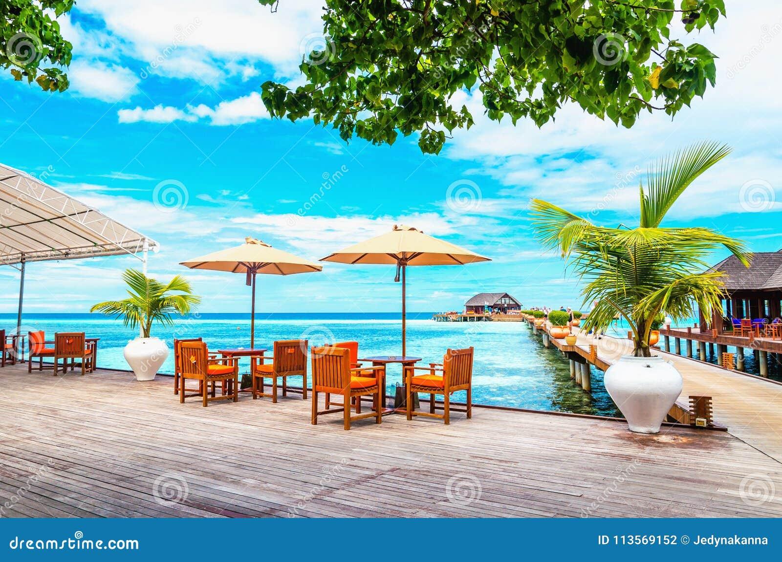 表和椅子与阳伞在一个木码头反对海洋和木平房的天蓝色的水的