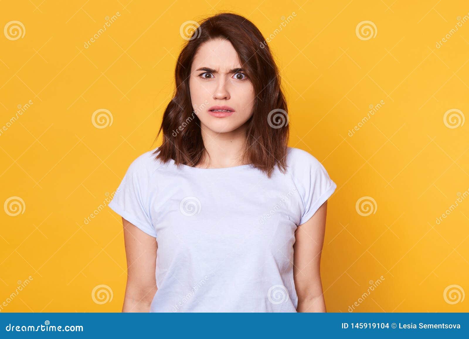 表现出的便服的深色的妇女憎恶,烦恶某事,有张看起来皱眉的面孔 Cauasian妇女与