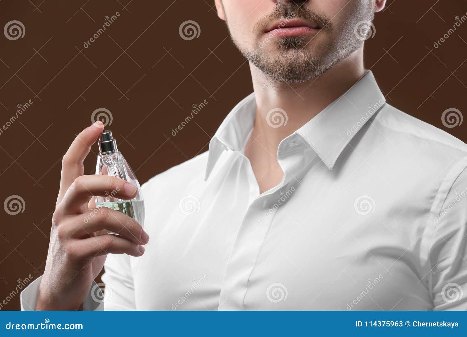 衬衣的英俊的人使用香水