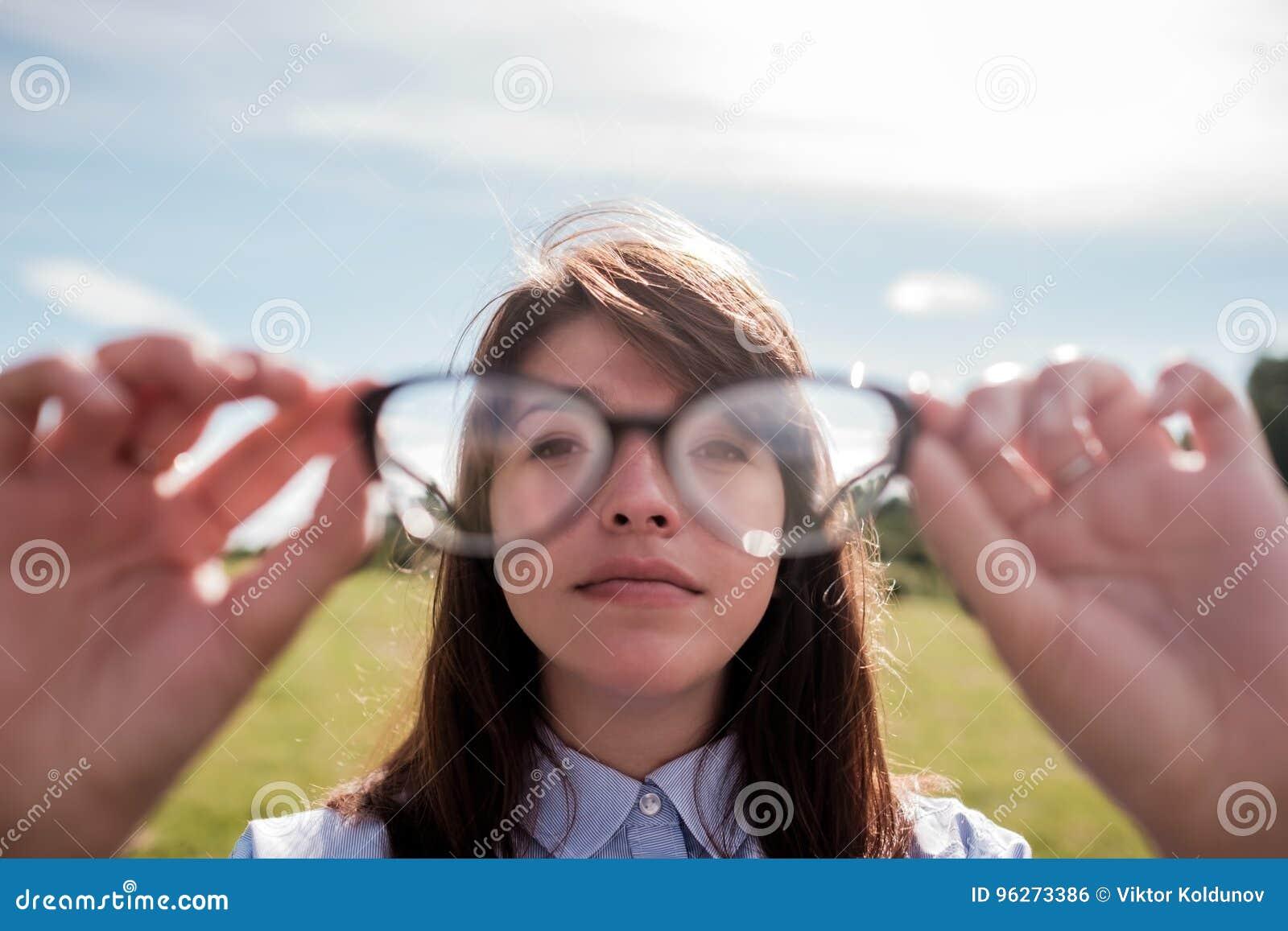 衬衣的年轻美丽的女孩有长的头发的通过玻璃看