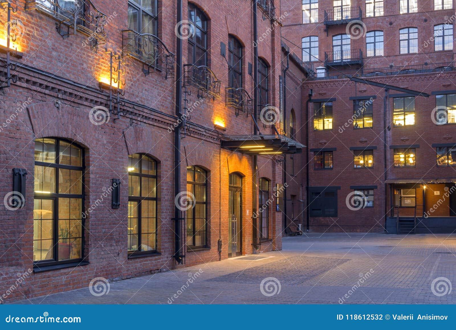 被停泊的晚上端口船视图 位于老工厂厂房的现代顶楼式办公室 砖安置红色 葡萄酒 与大Windows的大厦