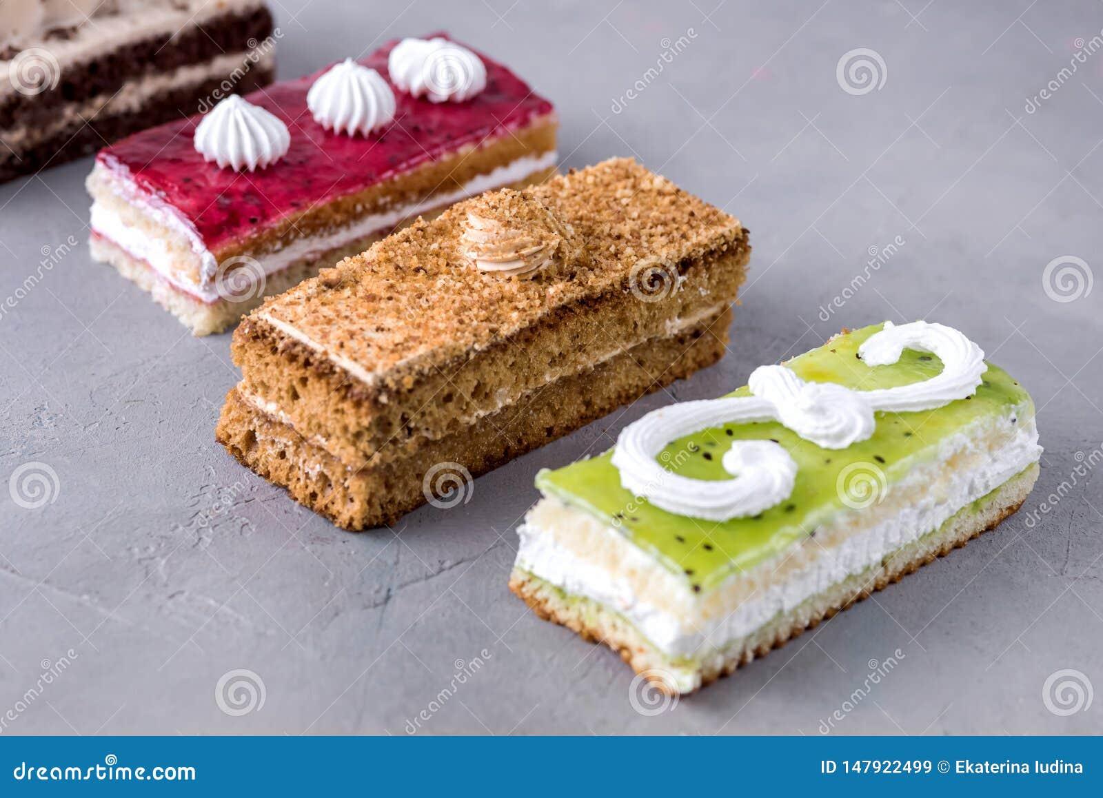 被分类的不同的微型蛋糕用奶油色咖啡巧克力盐溶了焦糖和莓果在水平的鲜美微型蛋糕点心上