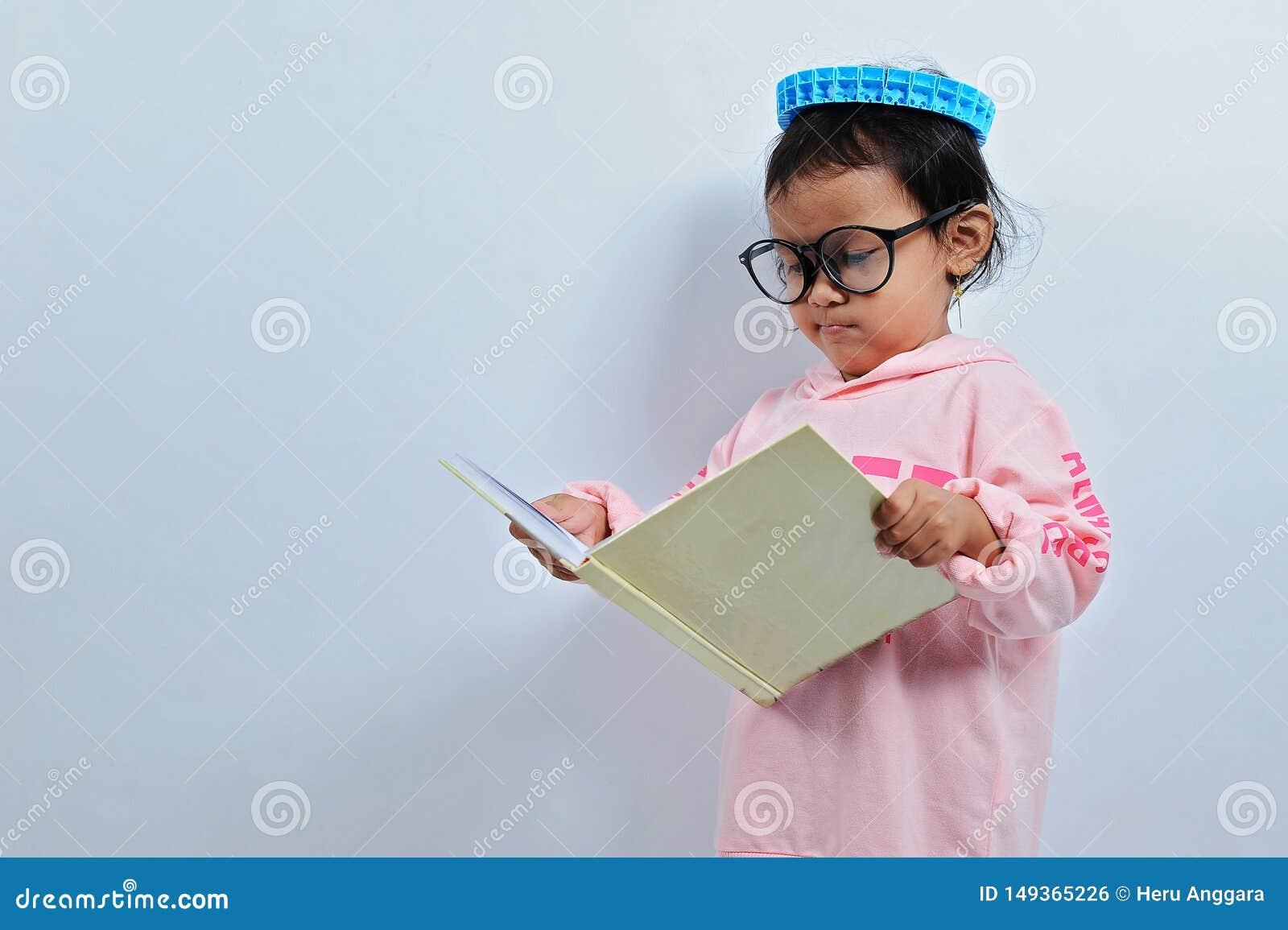 被切开的亚洲女孩穿戴玻璃然后打开书并且读书seriusly