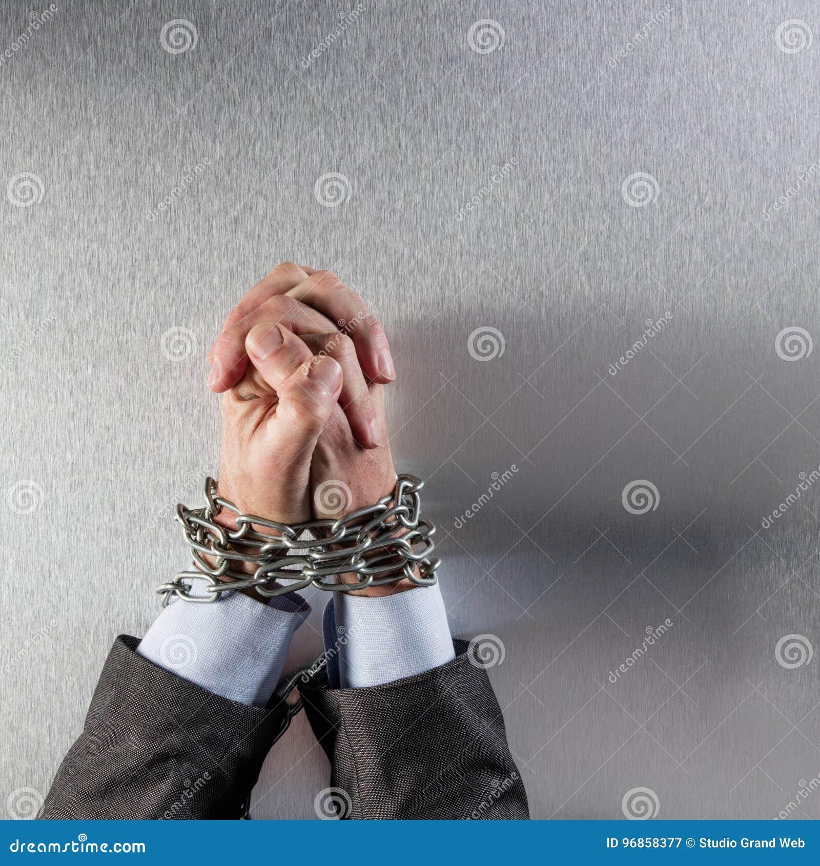 被加入的商人手绑住与祈祷为公司罪行的链子