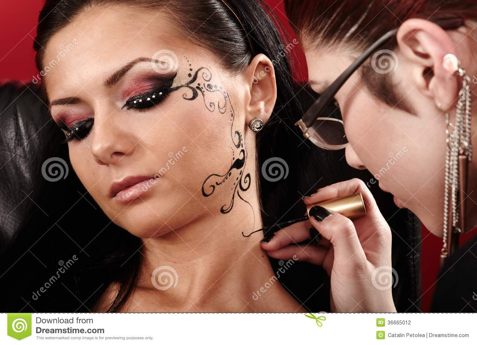被应用面孔纹身花刺的浅黑肤色的男人的特写镜头由化妆师.