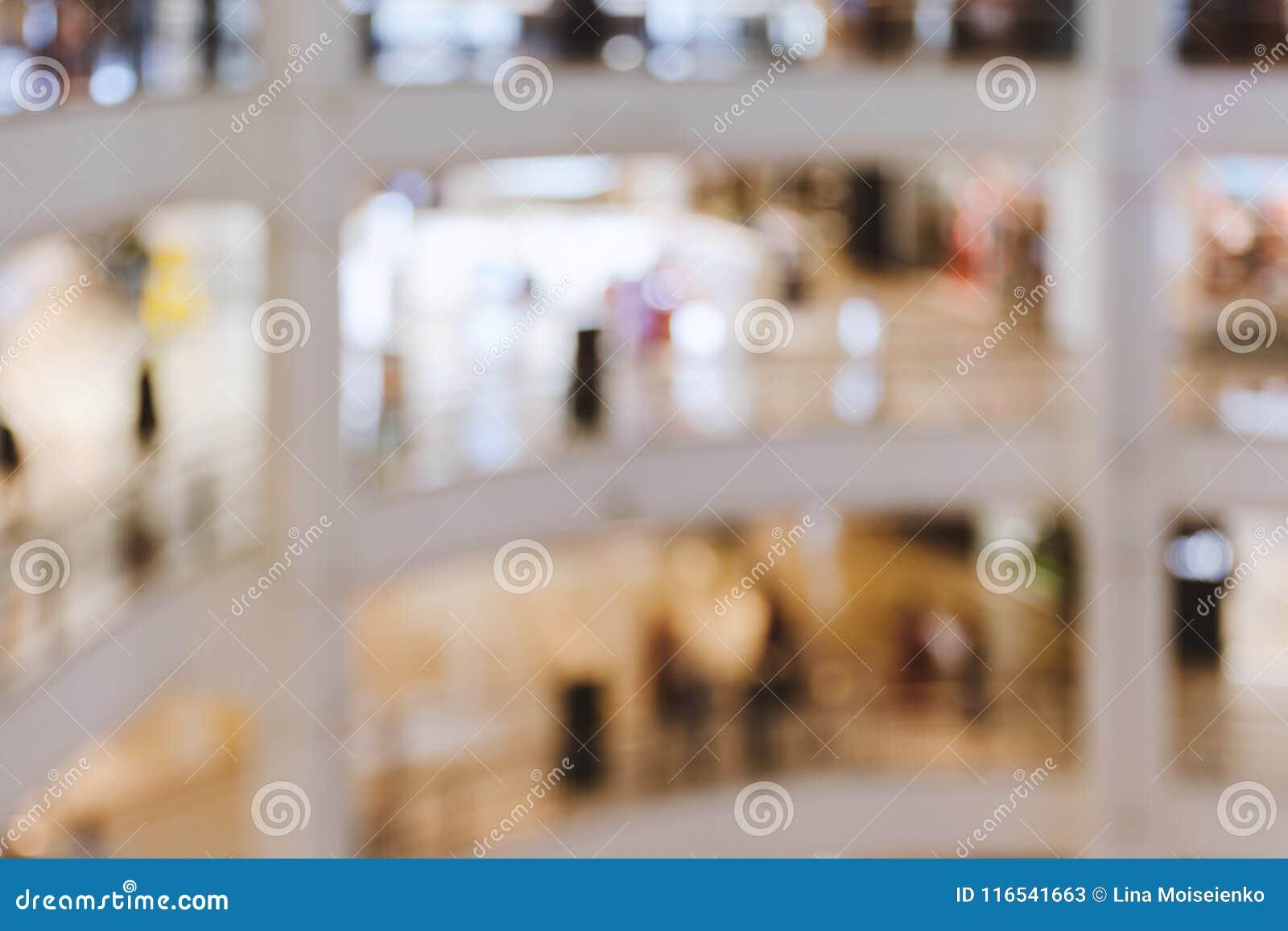 被弄脏的图象,浅景深-大多层的购物中心内部与温暖的光,人们的
