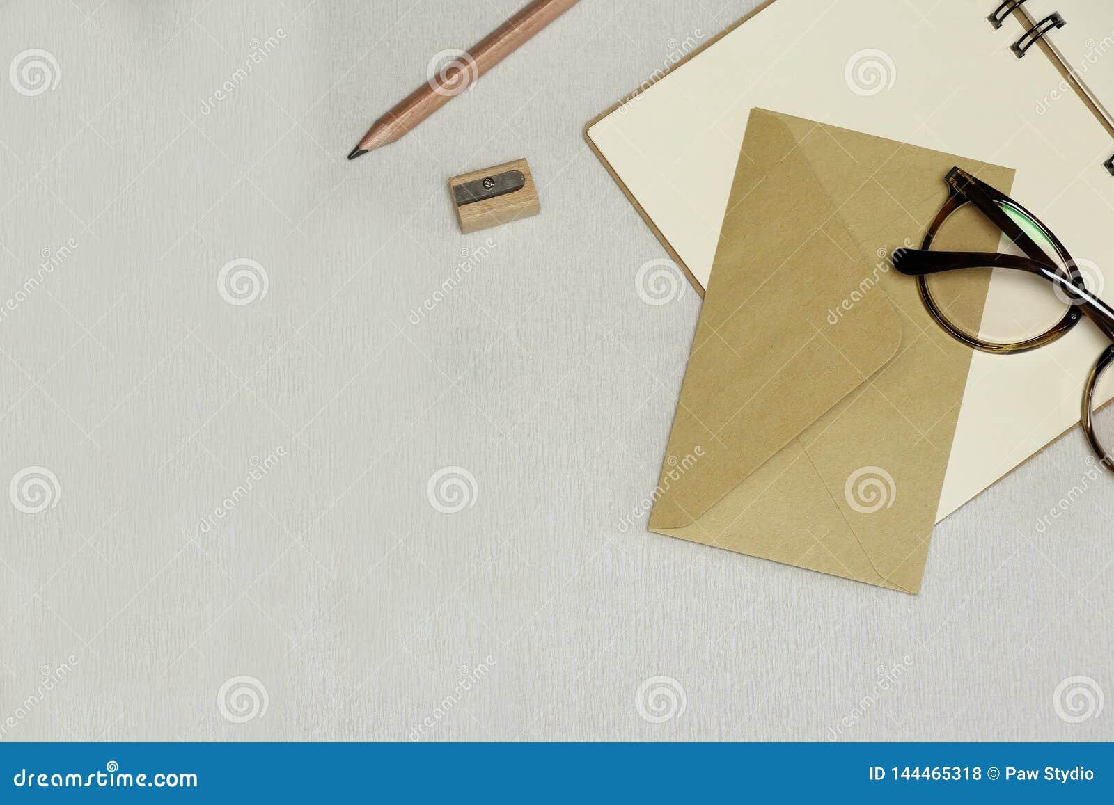 被打开的笔记本,铅笔,磨削器,信封,在白色背景的眼镜