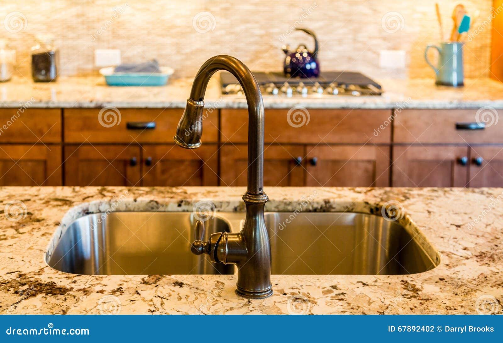 被摩擦的古铜色厨房水槽和装置