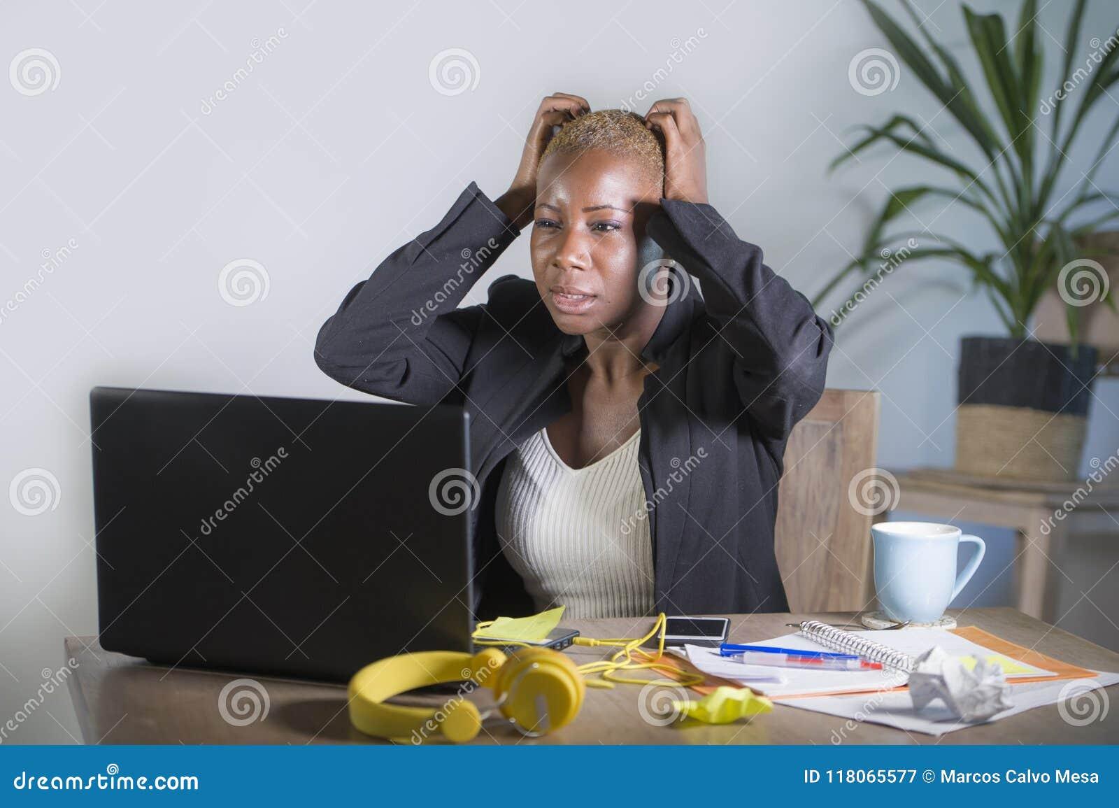 被注重的和被挫败的美国黑人的黑人妇女工作被淹没和被弄翻在办公室便携式计算机书桌打手势哀伤和d