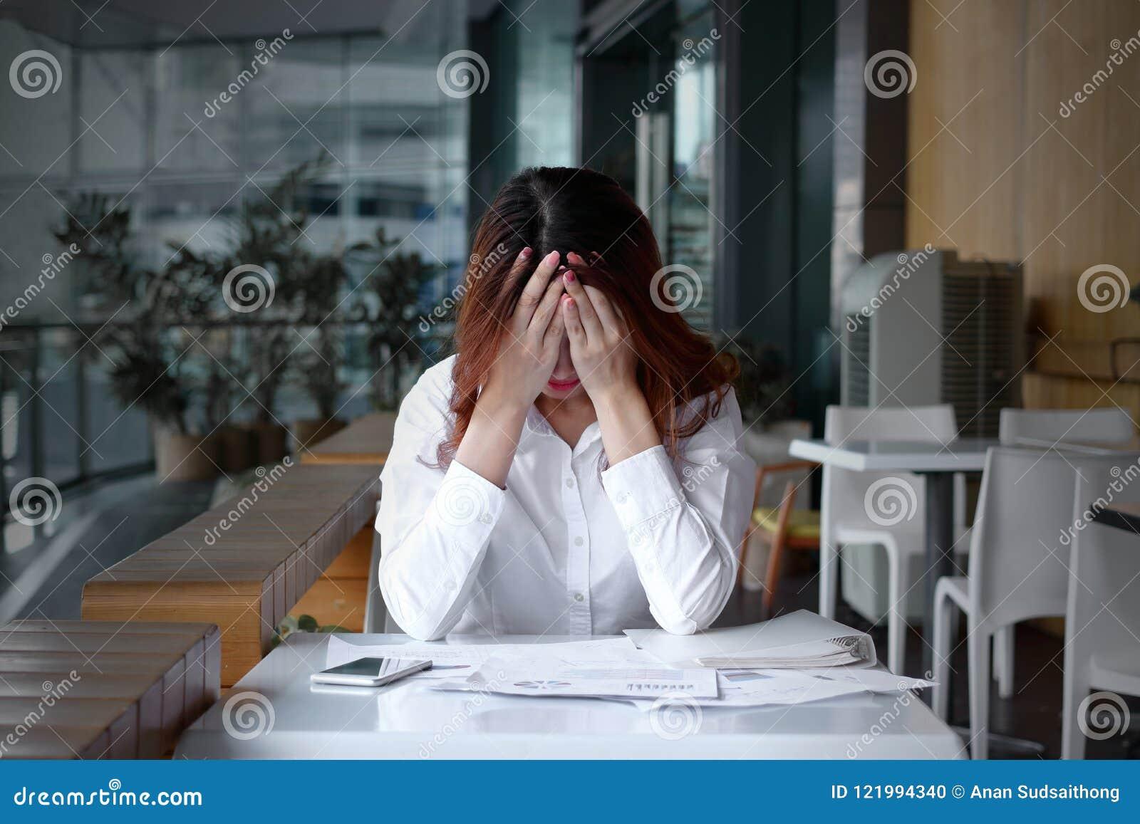 被注重的沮丧的年轻亚洲女商人覆盖物面孔正面图用在书桌上的手在办公室