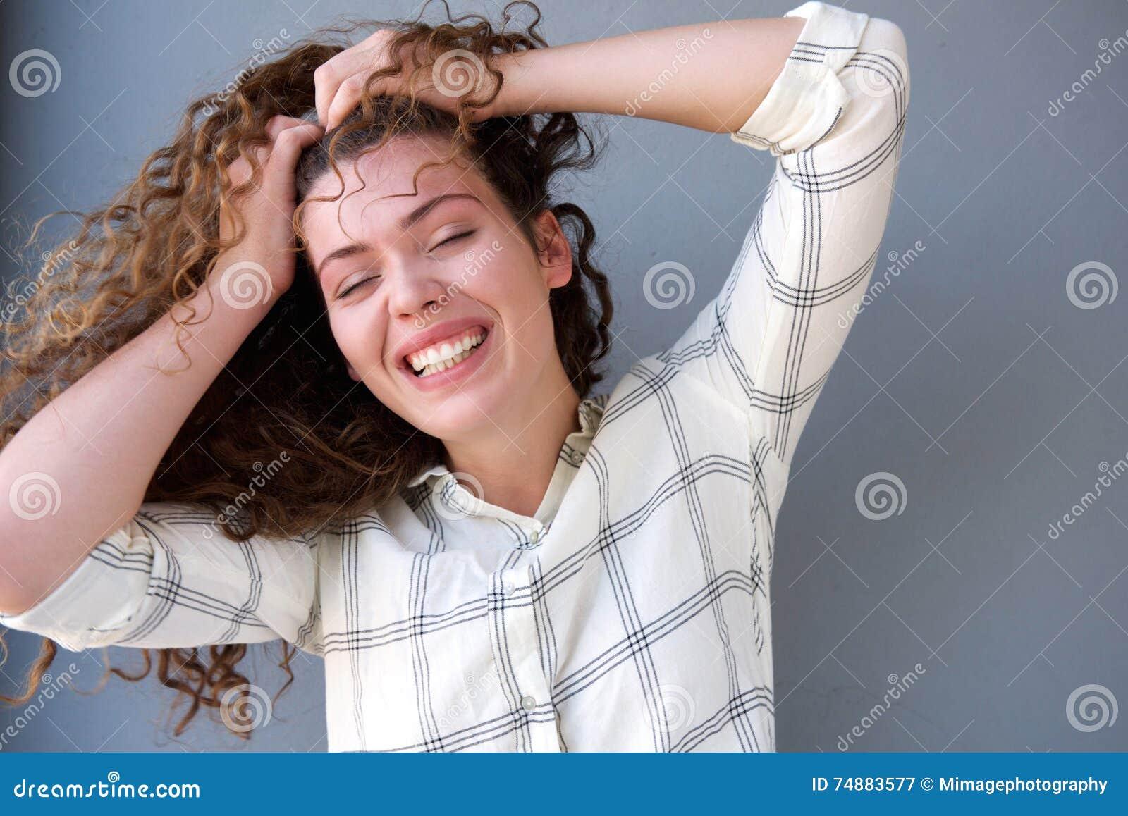 被注重的青少年的女孩用在头发和眼睛的手关闭了