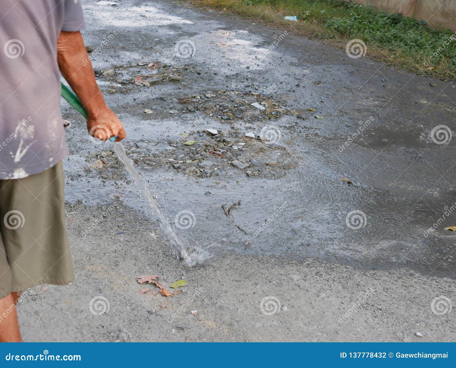 被浇灌的一条多灰尘的路防止通过在土路的车将踢的尘土