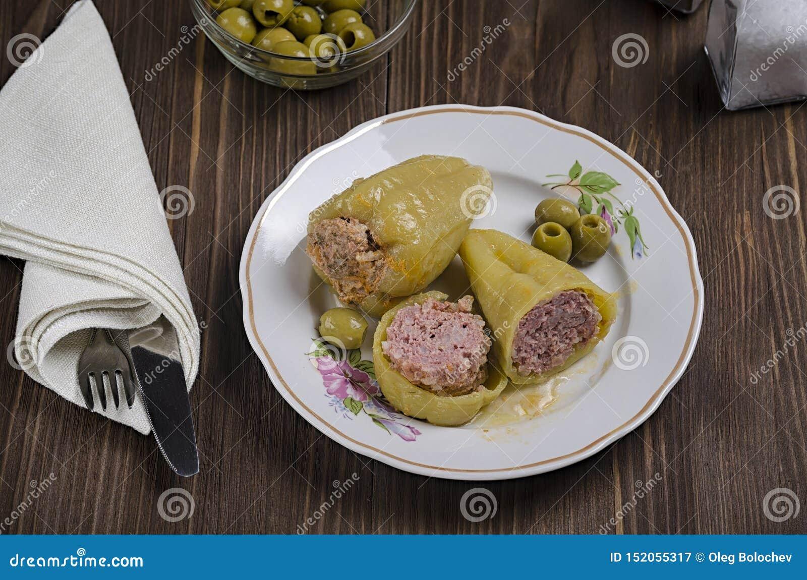 被炖的青椒充塞用在木背景的肉,用橄榄和盐在烧瓶,顶视图