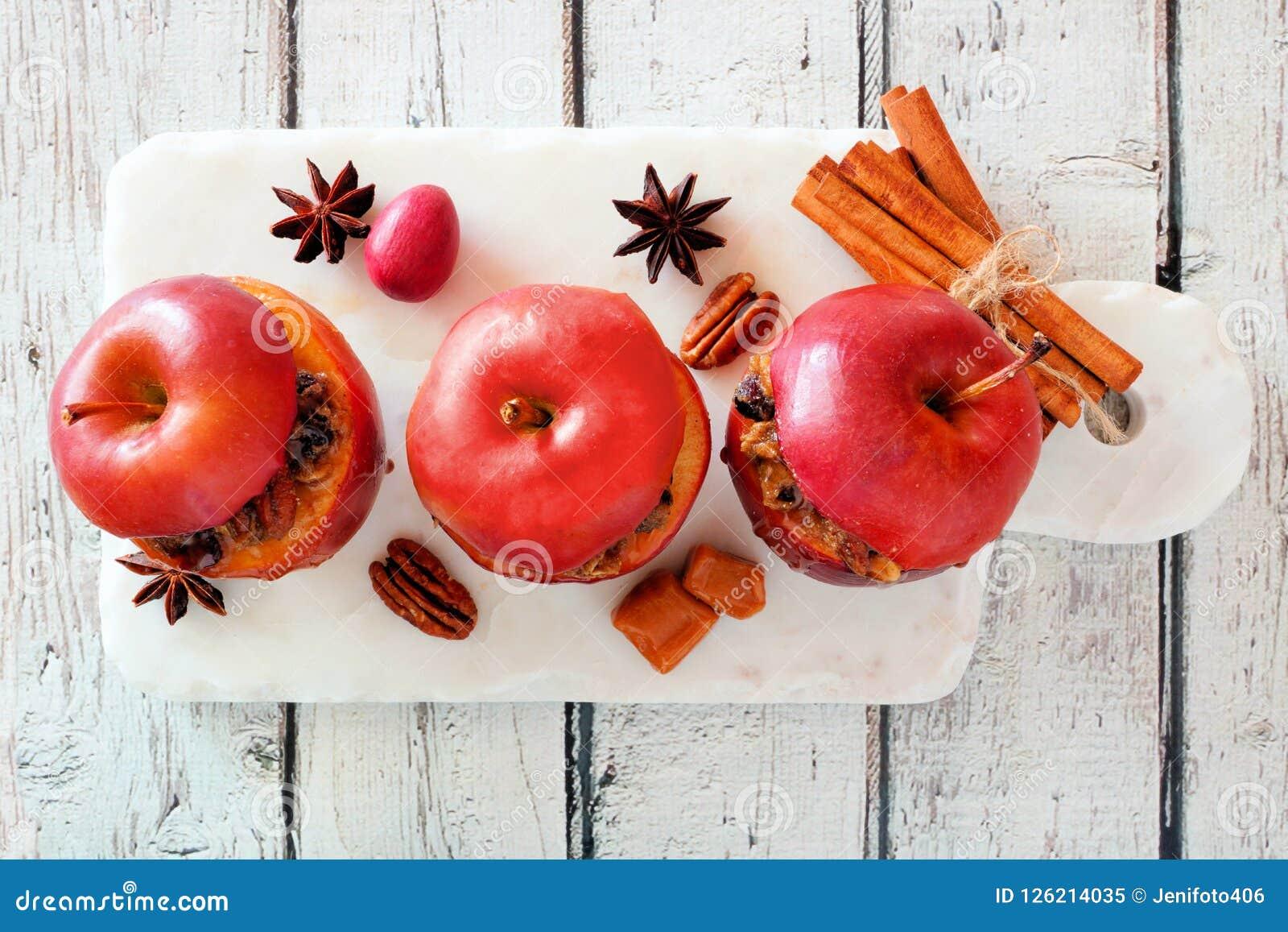 被烘烤的苹果用焦糖、红糖和和坚果,在白色木头的顶视图