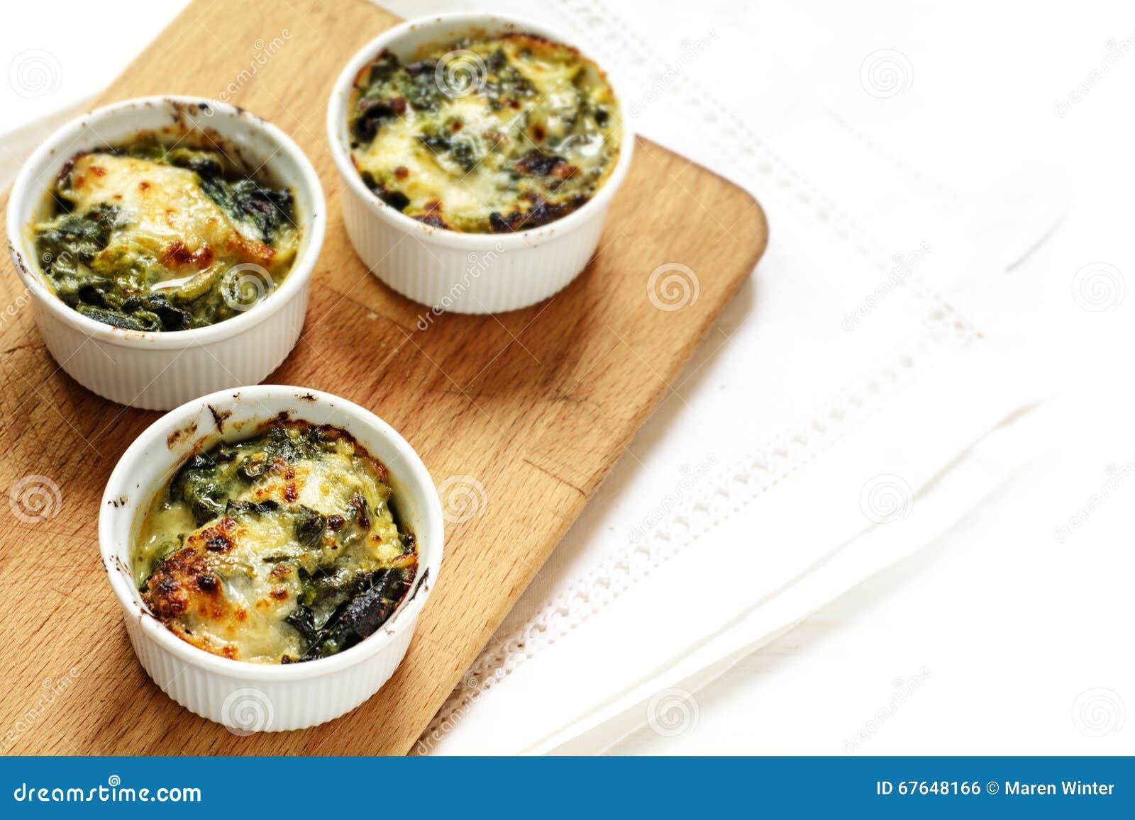 被烘烤的菠菜用在三个小砂锅盘的乳酪在a