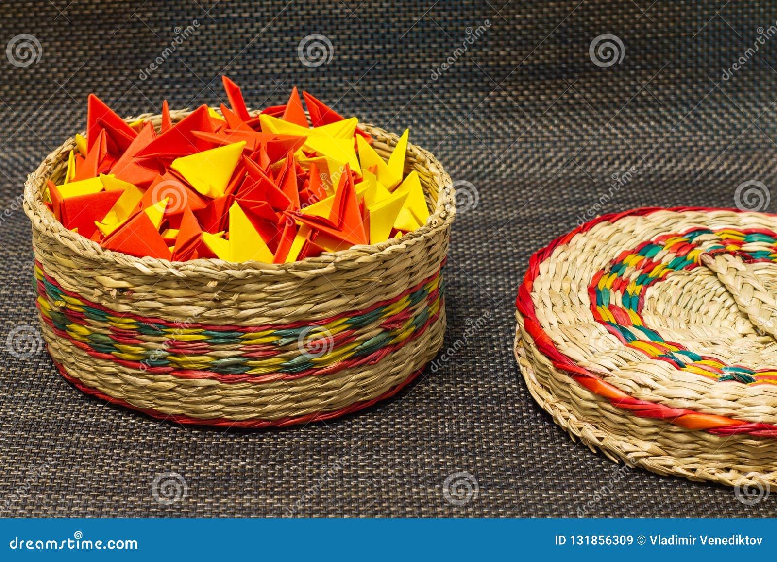 被编织的秸杆篮子与五颜六色的纸的