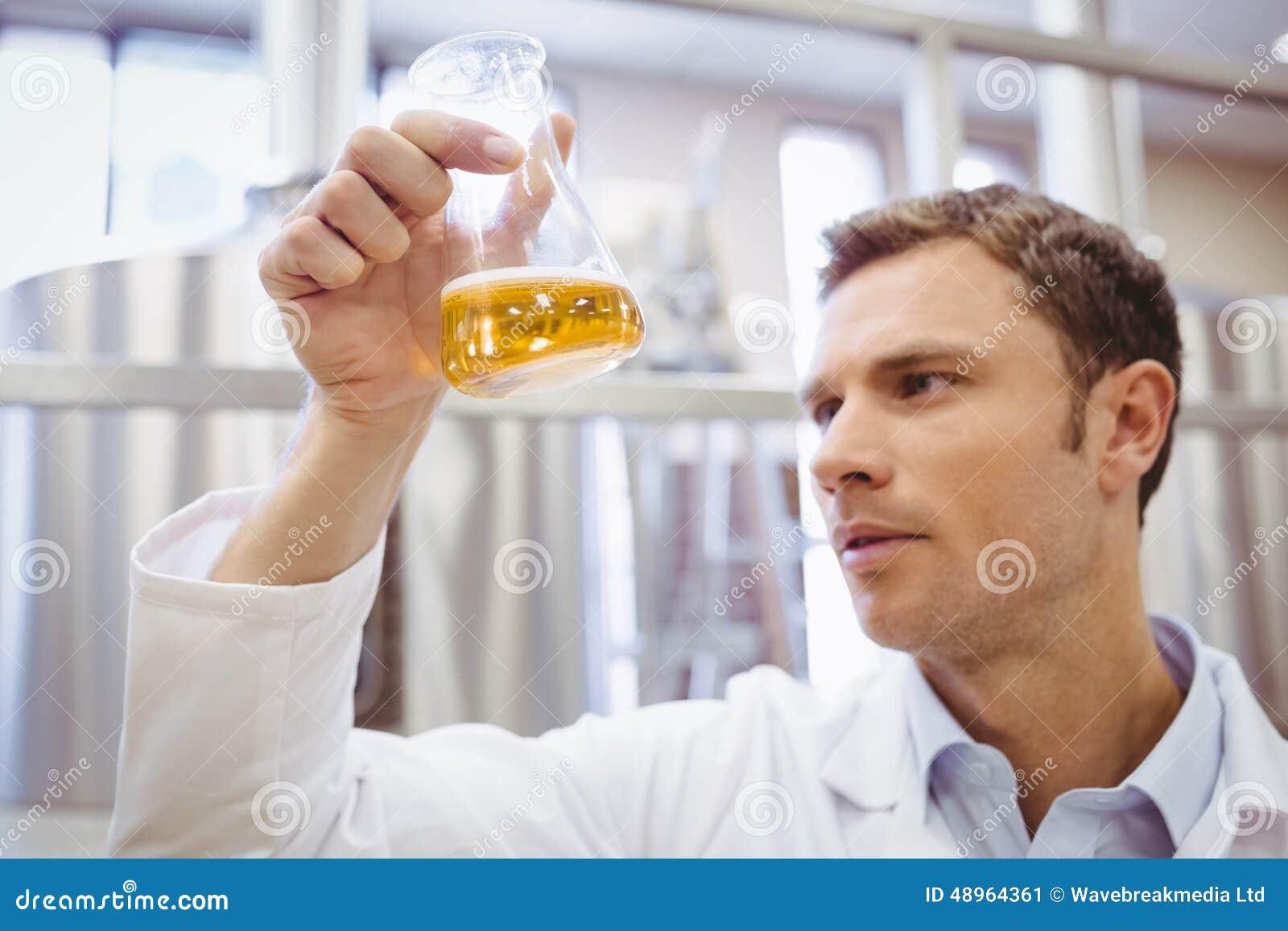 被聚焦的科学家审查的烧杯用啤酒